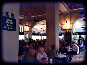 Im Cafe du Monde mit vielen Menschen an kleinen Tischen sitzen