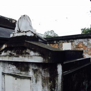 Grab auf dem Friedhof mit kaputter Skulptur