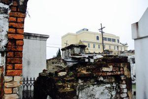 Verfallenes Grab und dahinter neue Häuser