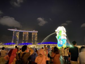 Blick auf Marina Bay Sands mit Merlion in Singapur abends