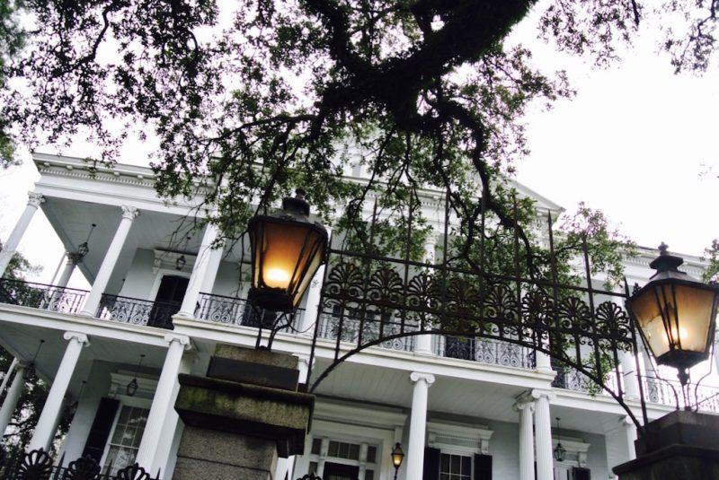 New Orleans im Garden District, Villa im Hintergrund und davor Lampen des Eingangs am Zaun