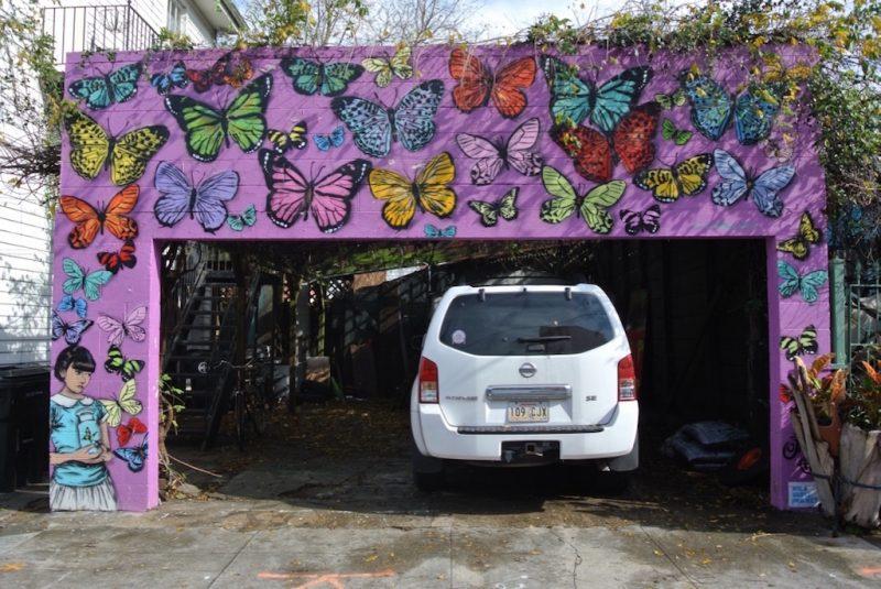 New Orleans, pinke Garageneinfahrt mit Strassenkunst aus Schmetterlingen und Mädchen