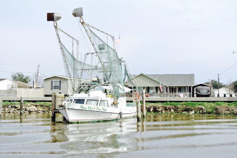 Unterwegs im Feuchtgebiet mit dem Boot und Louisiana Swap Tours, Sicht aufs Ufer mit Haus und Boot