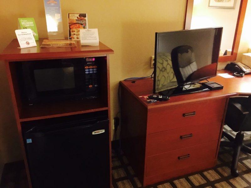 Zimmer mit Fernseher, Mikrowelle, Kühlschrank und Infomaterial