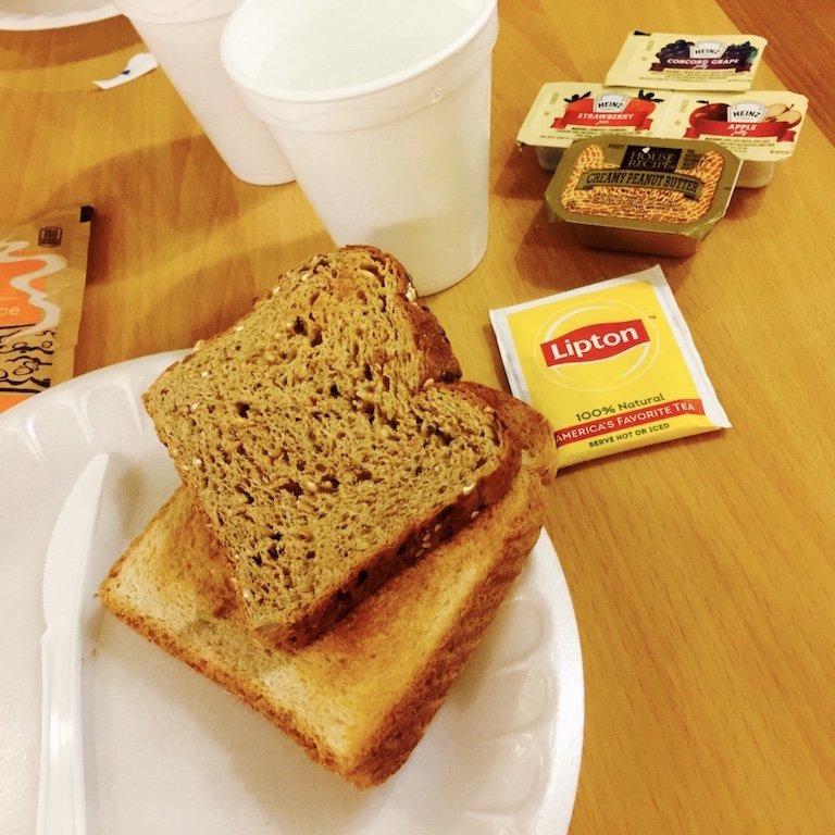 Mein Frühstuck auf dem Tisch mit Toast, Tee, Marmeladen und Erdnussbutter alles noch eingepackt