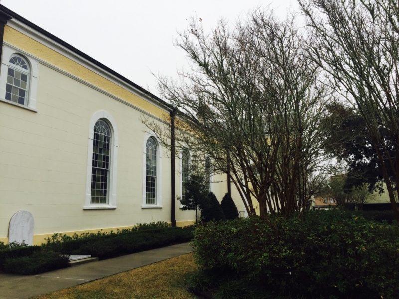 Seitliche Ansicht der gelben Kirche in St. Martinville mit Bäumen davor