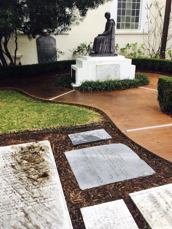 Seitliche Sicht auf Evangeline Skulptur im Hintergrund und liegenden Grabsteinen im Vordergrund