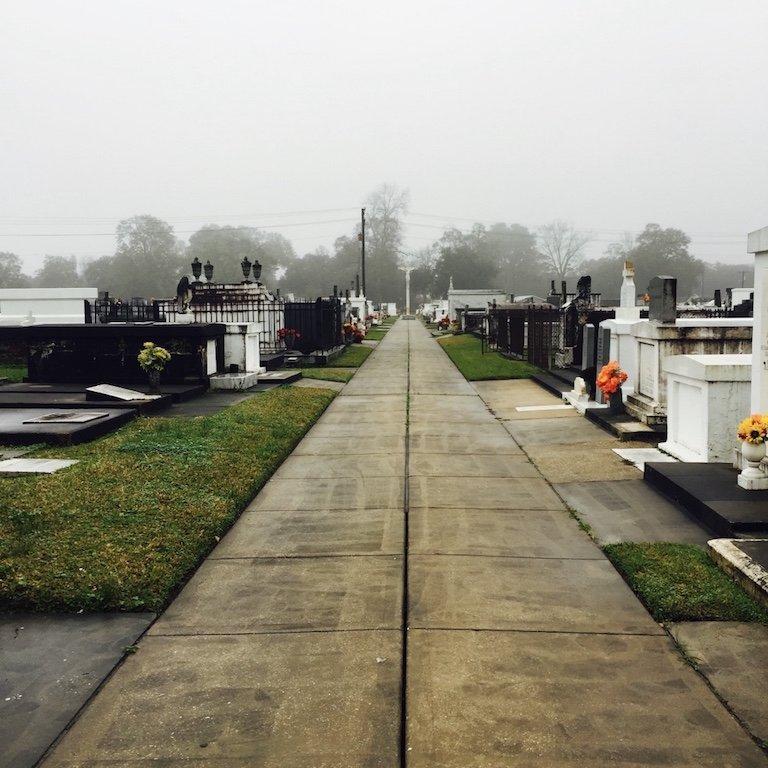 Gräberreihe rechts und links an einem nebligen Tag in St. Martinville