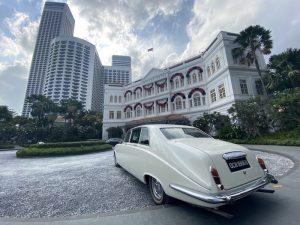 Raffles Hotel aussen - Fassade seitlich fotografiert mit Oldtimer
