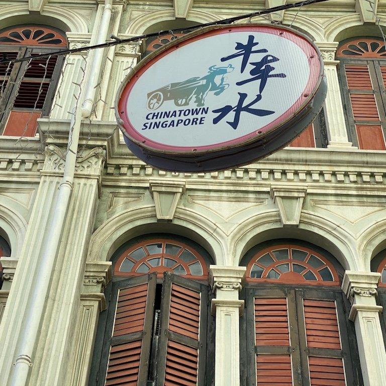 Schild mit Singapur und Chinatown Aufschrift vor Haeuserfassade