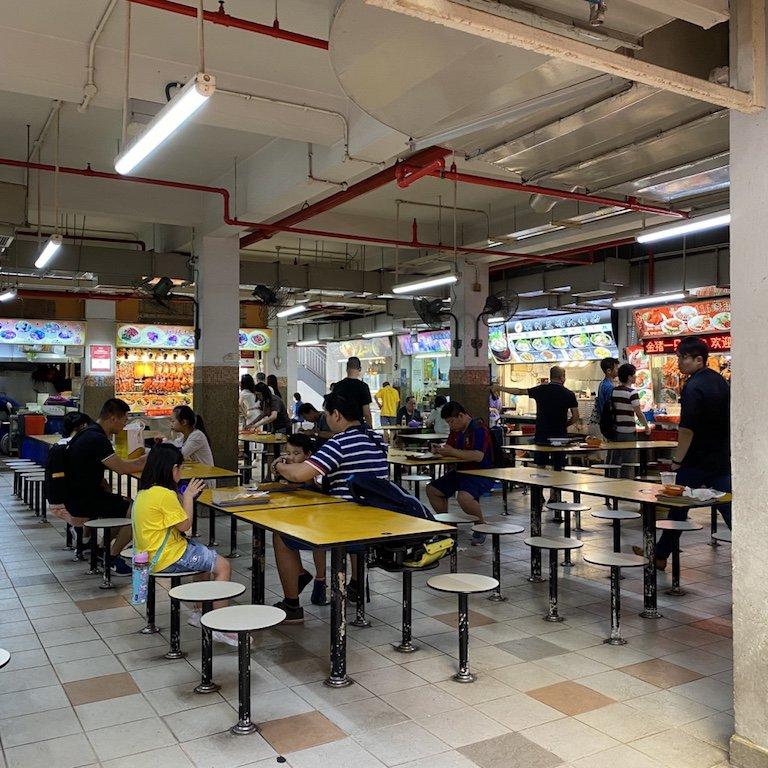 Tische und Stände im Hintergrund in einem Hawker Centre in Chinatown in Singapur