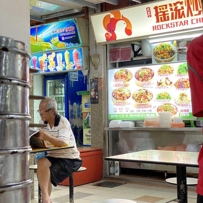 Essensstand in einem Hawker Centre in Chinatown mit lesenden Mann an einem Tisch