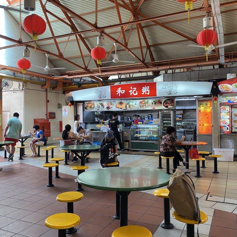 Tische und Stände im Hintergrund in einem Maxwell Hawker Centre in Chinatown in Singapur