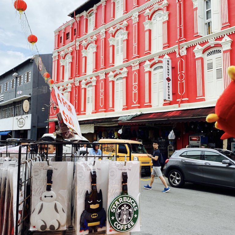 Strasse mit restaurierter Hausfassade in rot und