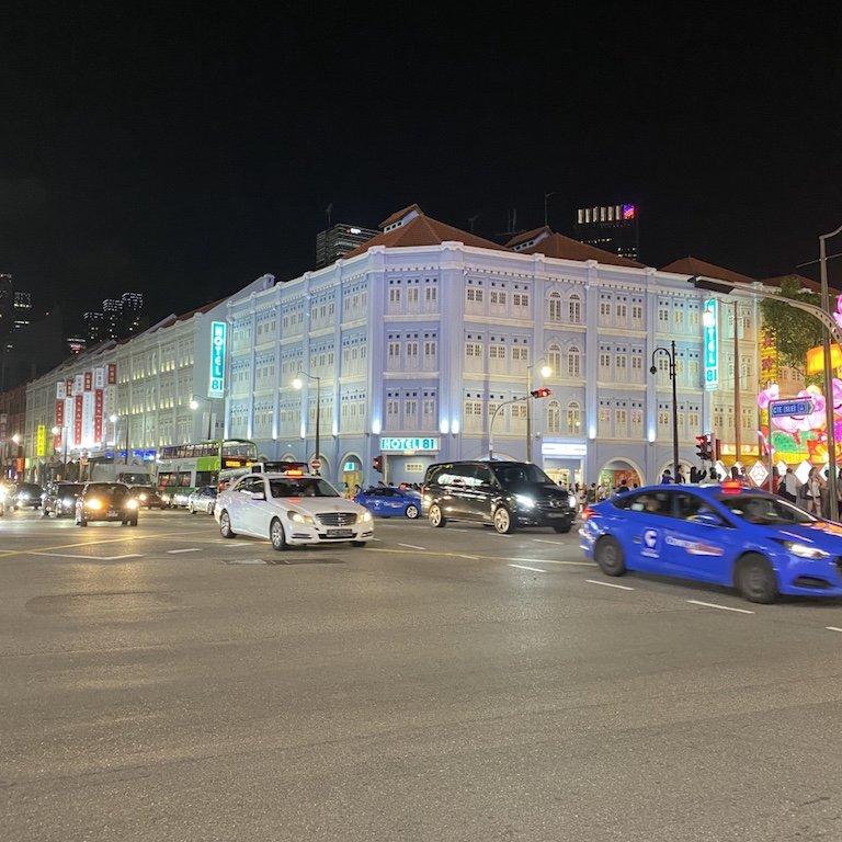 Belebte und beleuchtete Strasse für Shopping bei Nacht in Chinatown mit Hotel 81 im Hintergrund