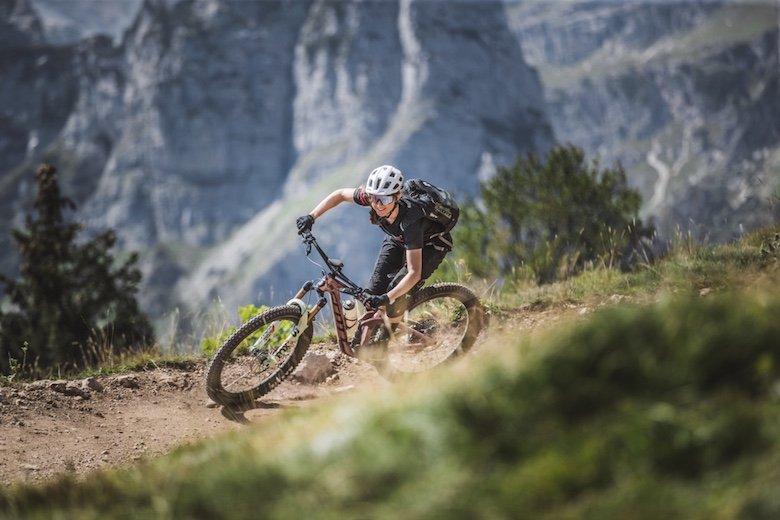 Radfahrer in Kurve mit Berge Brenda Dolomiten im Hintergrund